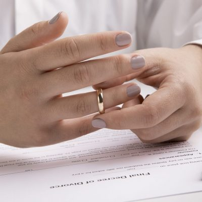 Marriage dissolution concept, close up view of hand taking off engagement ring, panorama