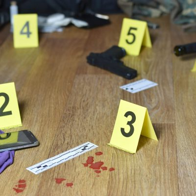 Id tents at crime scene after gunfight indoors. Blood and gun cartridges as evidence on crime scene investigation process close up